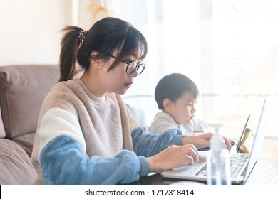 Young Asian mother working on a modern laptop from home with her child watching cartoon on a tablet during the coronavirus pandemic lockdown social distancing