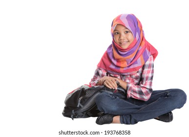 Young Asian Muslim girl with a backpack sitting on the floor