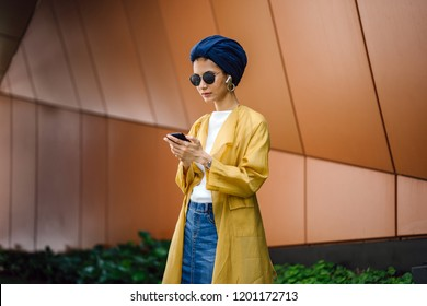 A young Asian (Muslim Malay) woman in a turban and sunglasses is streaming and listening to music via her wireless earphones during the day.