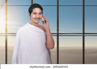 Young asian muslim man with ihram cloth using cellphone with window glass background
