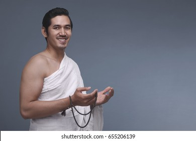 Young asian muslim man in ihram holding prayer beads against dark background