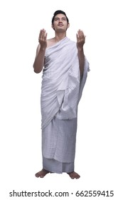 Young asian muslim man with ihram praying isolated over white background
