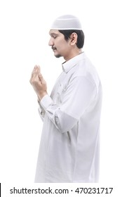 Young asian muslim man praying to god, muslim dress and wear caps with isolated background