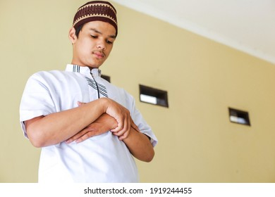 Young asian muslim man stands with hand in chest are doing salat  - Shutterstock ID 1919244455