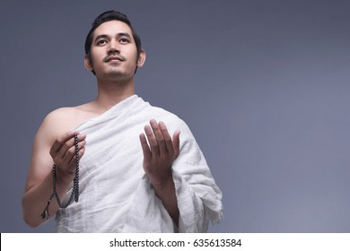 Young asian muslim man wearing ihram clothes with prayer beads against dark background