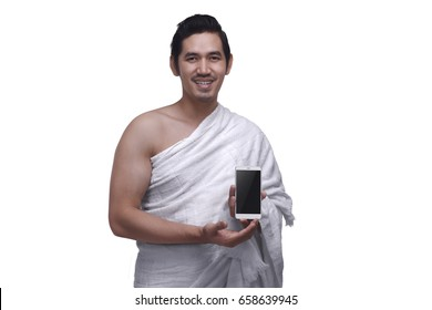 Young asian muslim man wearing ihram dress holding phone isolated over white background