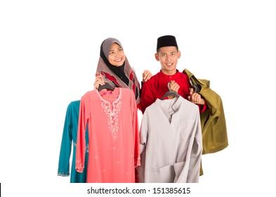 Young Asian Muslim man and woman posses shopping with Baju Kurung and Baju Melayu in action.