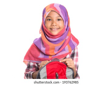 Young Asian Muslim school girl with head scarf carrying a backpack over white background