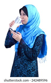 Young Asian muslim woman drinking a glass of milk isolated on white background