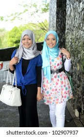 Young asian Muslim woman in head scarf walk together with handbag
