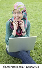 Young asian muslim woman in head scarf smile with laptop