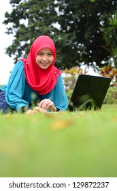 Young asian muslim woman in head scarf smile at park