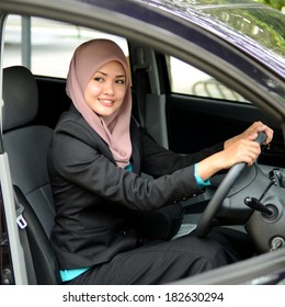 Young asian muslim woman in head scarf smile inside the car