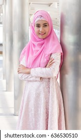 Young asian muslim woman in head scarf smile with arms crossed smiling and standing at capital city. Beautiful Muslim women. Thai Muslim women.