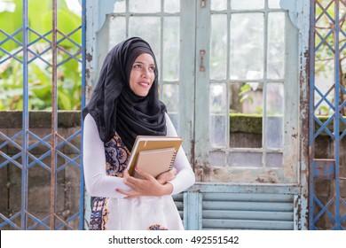 Young asian muslim woman holding notebook.Young asian muslim w