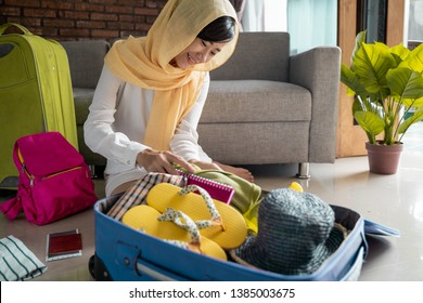young asian muslim woman put stuff in suitcase. concept of female with head scarf travelling