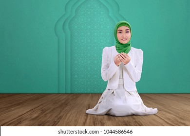 Young asian muslim woman sitting and praying with green wall background