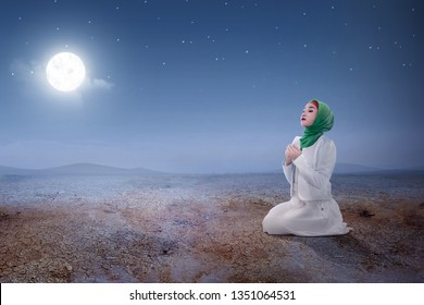 Young asian muslim woman sitting in pray position while raised hands and praying on the sand dune with moon and night scene background