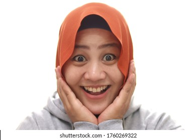 Young Asian muslim woman wearing hijab with surprised excited happy screaming. Cheerful girl with funny joyful face expression, hands holding face, isolated on white
