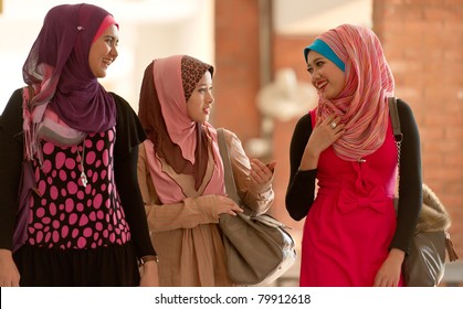 Young Asian Muslim women talking each others while walking