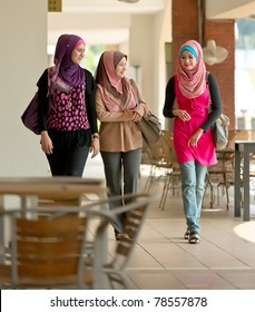 Young Asian Muslim women walking together at coffee shop