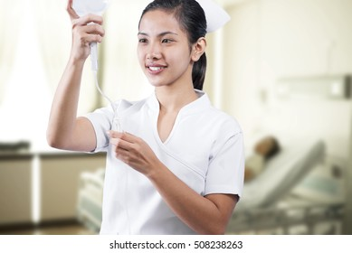 Young asian nurse preparing IV fluids for a patient. A patient lying in a hospital  bed at the background.