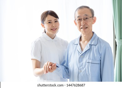 young asian nurse with senior patient in hospital