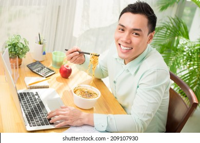 Young Asian office worker eating instant noodle while working on laptop