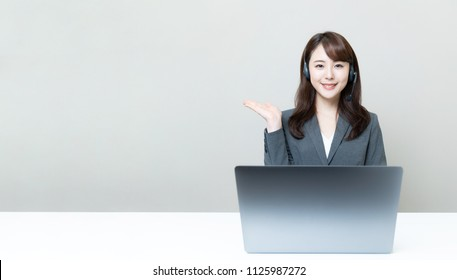 Young asian operator pointing at copy space.