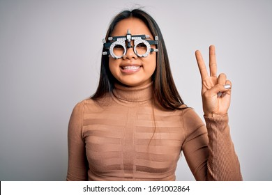 Young asian optical girl controlling eyesight using optometry glasses over white background smiling with happy face winking at the camera doing victory sign. Number two.