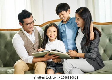 young asian parents and two children sitting on couch reading book together in family living room at home