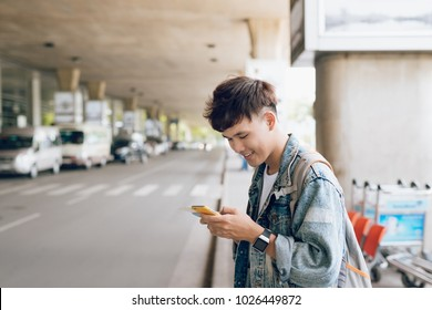 Young asian passenger waiting for taxi at the airport with phone