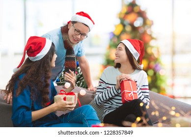 Young asian people ,a man and two women talking in Christmas party.