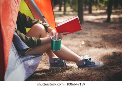 Young asian people enjoy camping in forest at summer,reading book inside tent and drinking coffee,hiking,teamwork,travel concept.