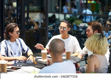 young asian people man and woman relaxing chatting in outdoor coffee shop