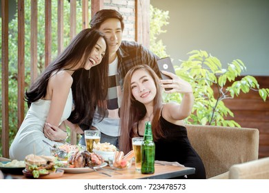 Young Asian peoples are selfie together on a day of party. On the table, there are many beer and food.