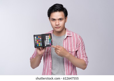 Young asian photographer holding color checker card, while working in studio