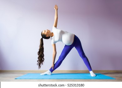 Young asian pregnant woman doing yoga at home