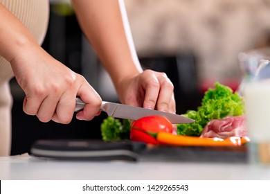 Young asian pregnant woman in ketchen. Cutting vegetable with large knief. Parenthood concept.