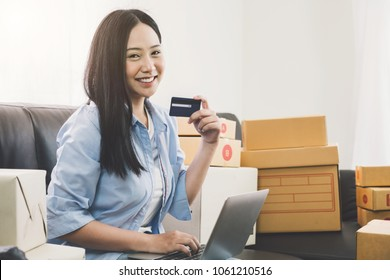 Young asian pretty girl using credit card and laptop computer for shopping online at home