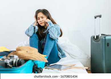 young asian pretty woman hipster traveler sad after flight cancelled with packing clothes into suitcase for holiday vacation on bed at home, delayed flight, summer holiday, backpacker, travel concept