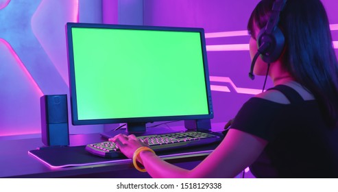 Young Asian Pro Gamer Playing in Online Video Game with green chroma key screen computer