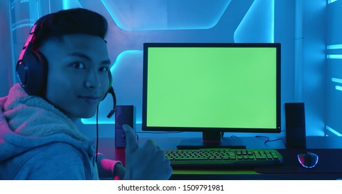 Young Asian Pro Gamer show thumb up with green chroma key screen computer - Focus on monitor
