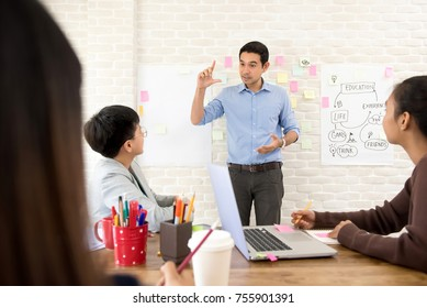 Young Asian professional male teacher teaching and explaining college students in classroom - learning and education concepts