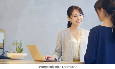 Young asian receptionist talking with customers. Hotel worker. Store clerk.