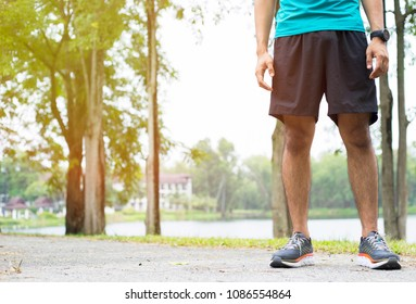 Young Asian runner athletic man legs start running in park