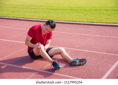 Young asian runner having pain at knee between running in stadium