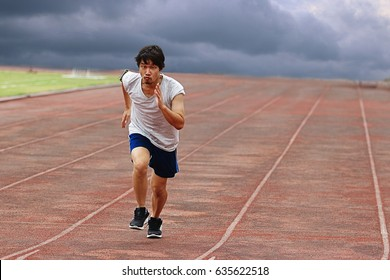 Young Asian runner running on track with weather storm background.