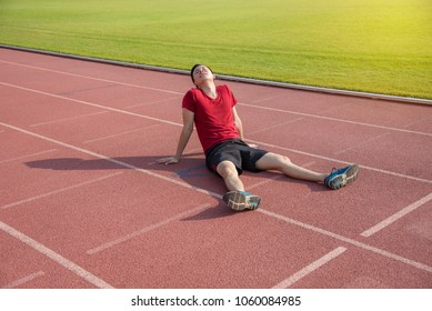 Young asian runner sitting on the ground after losing in competition