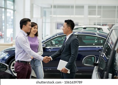 Young Asian salesman greeting couple in car dealership
